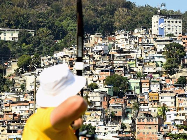 Một vận động viên người Úc đang ngắm bắn, đằng xa là khung cảnh khu ổ chuột Rio favela nổi tiếng.