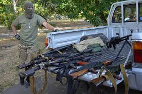 Một lái súng chào lô hàng vũ khí với nhóm phóng viên kênh truyền hình Sky News.