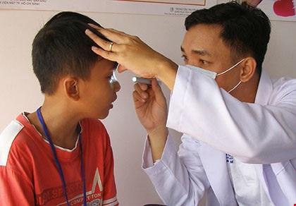 BS chuyên khoa đang khám tật khúc xạ mắt cho học sinh. Ảnh: TRẦN NGỌC