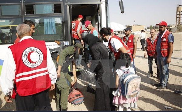 Nhân viên Hội Trăng lưỡi liềm Đỏ Syria hỗ trợ người dân sơ tán khỏi Daraya tới trại tị nạn Herjelleh ở gần Damascus. (Nguồn: EPA/TTXVN)