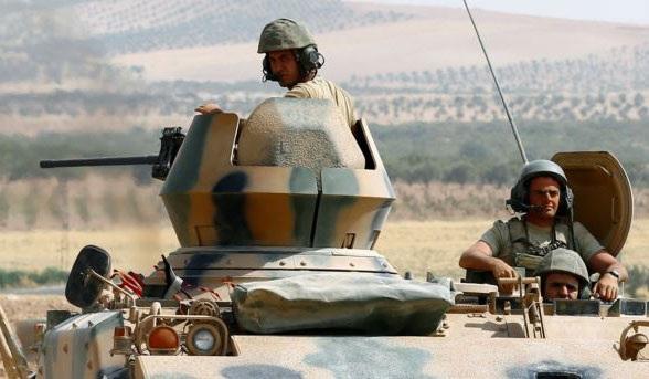 Lính Thổ Nhĩ Kỳ ngồi trên xe tăng trong đoàn xe quân sự tiến vào con đường chính ở Karkamis, vùng biên giới Thổ Nhĩ Kỳ-Syria ở tỉnh Gaziantep. Ảnh: Reuters