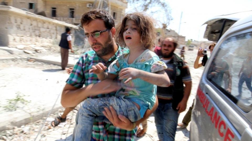 Người đàn ông bế một bé gái sống sót sau đợt không kích của quân đội Chính phủ Syria và quân đội Nga hôm 27/8 ở gần khu vực Aleppo. (Nguồn: Aljazeera)