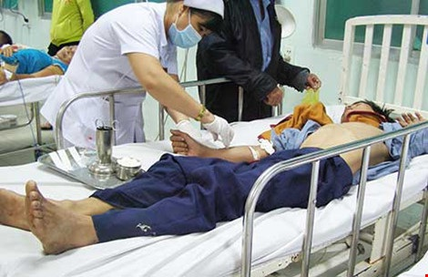 Xoay xở một hồi, nhân viên y tá mới có thể tiêm thuốc cho người thanh niên uống thuốc trừ sâu. Ảnh: TRẦN NGỌC