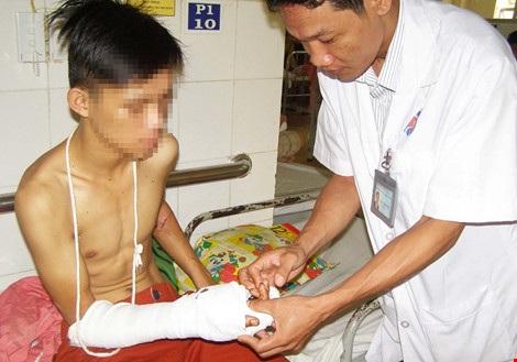BS Võ Thành Trung đang kiểm tra bàn tay đứt lìa của bệnh nhân. Ảnh: TRẦN NGỌC