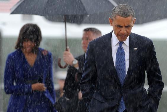 Tổng thống Mỹ Barack Obama để đầu trần bước đi giữa cơn mưa. (Nguồn: Getty Images)