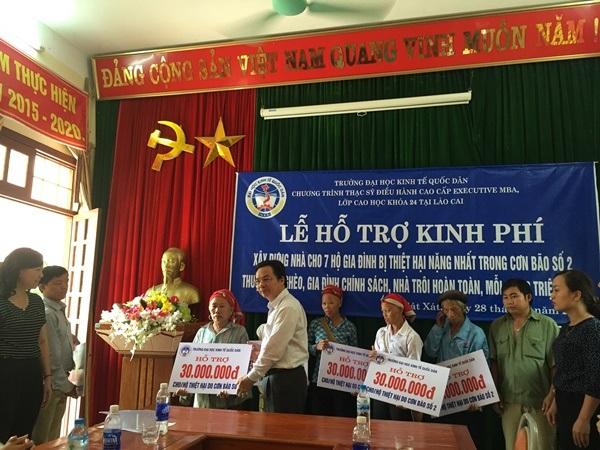 PGS.TS Hoàng Văn Cường, Phó Hiệu trưởng trường ĐH Kinh tế quốc dân trao tiền hỗ trợ tới hộ gia đình nghèo bị lũ cuốn trôi nhà cửa