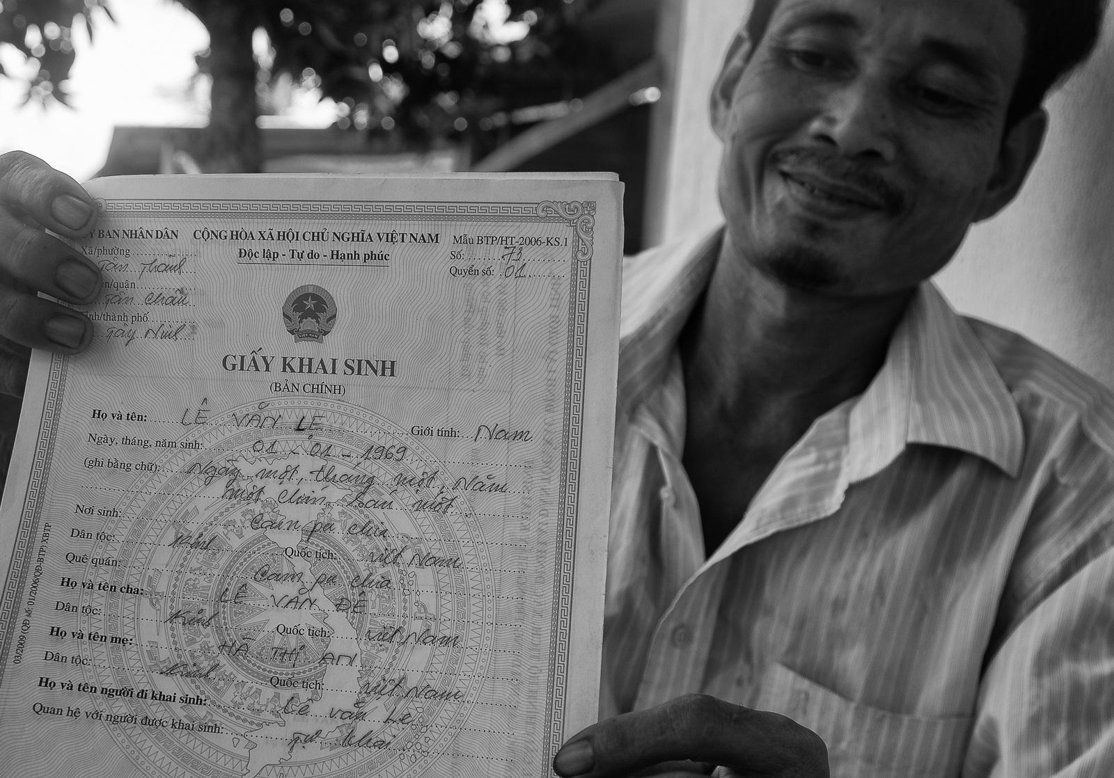 Ông Lê Văn Lẹ, một trong những Việt kiều được chính quyền công nhận quốc tịch Việt Nam. Trong ảnh là tờ giấy khai sinh ông vừa được cấp, phần quê quán ghi: Campuchia, phần quốc tịch ghi Việt Nam. Nhờ tờ giấy này, ông làm được CMND, hộ khẩu, các con được đi học, đi làm. Đến nay ông đã xây được nhà đàng hoàng.