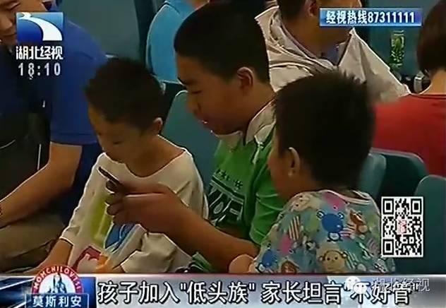 Bạn nhỏ 4-5 tuổi này chỉ nhìn chằm chằm vào màn hình chiếc điện thoại của bố mẹ mà không nói câu gì, bên cạnh bạn ấy còn có mấy bạn nhỏ khác vây quanh.
