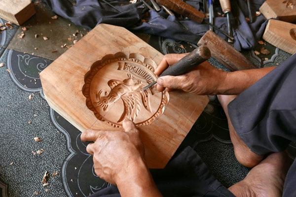 """Bằng đôi bàn tay khéo léo, ông Trần Văn Bản đã """"phù phép"""" những khối gỗ thành những khuôn bánh với đủ hình thù đẹp mắt."""