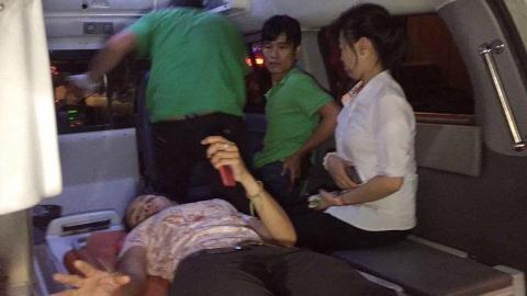 Một người phụ nữ được đưa lên xe cứu thương. Ảnh: Strait Times