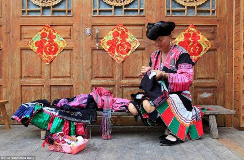 Nhiều phụ nữ Dao tại ngôi làng Huangluo được mời làm diễn viên hay bán đồ thổ cẩm cho du khách.