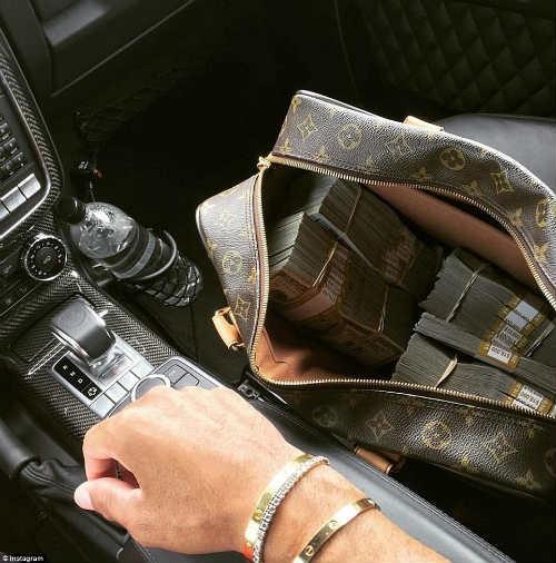 Anh chàng Danny Agha khoe chiếc túi chứa đầy tiền mặt