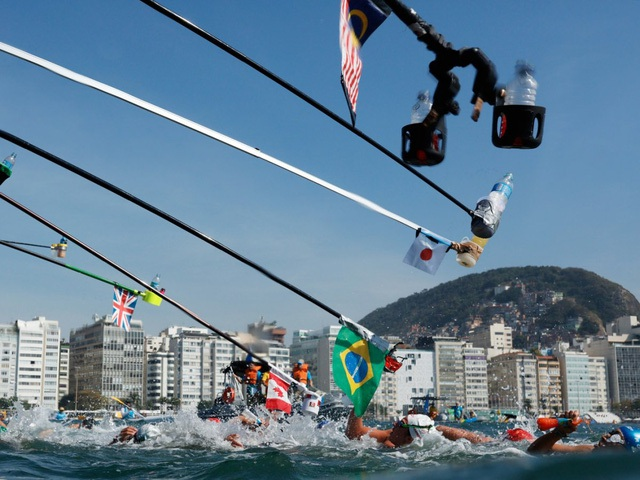 Các vận động viên môn bơi marathon cự ly 10 km tiếp nhận nước uống.