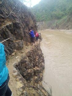 Các giáo viên trường mầm non Tà Mít đang nắm tay nhau vượt qua vách núi cheo leo, hiểm trở chỉ vừa đặt bàn chân, phía dưới là dòng sông đang cuồn cuộn chảy