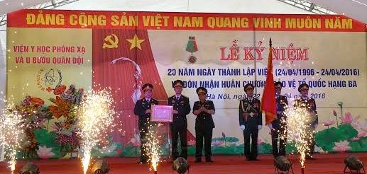 Đại tá, BS Nguyễn Trung Sơn, Giám đốc Viện Y học phóng xạ và ung bướu quân đội (thứ 2 từ trái sang) đón nhận Huân chương bảo vệ Tổ quốc hạng Ba của Chủ tịch nước (Ảnh: T.P)