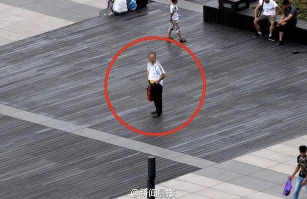Người đàn ông ôm chiếc quần sắp tụt ở giữa phố đông người của Thượng Hải.
