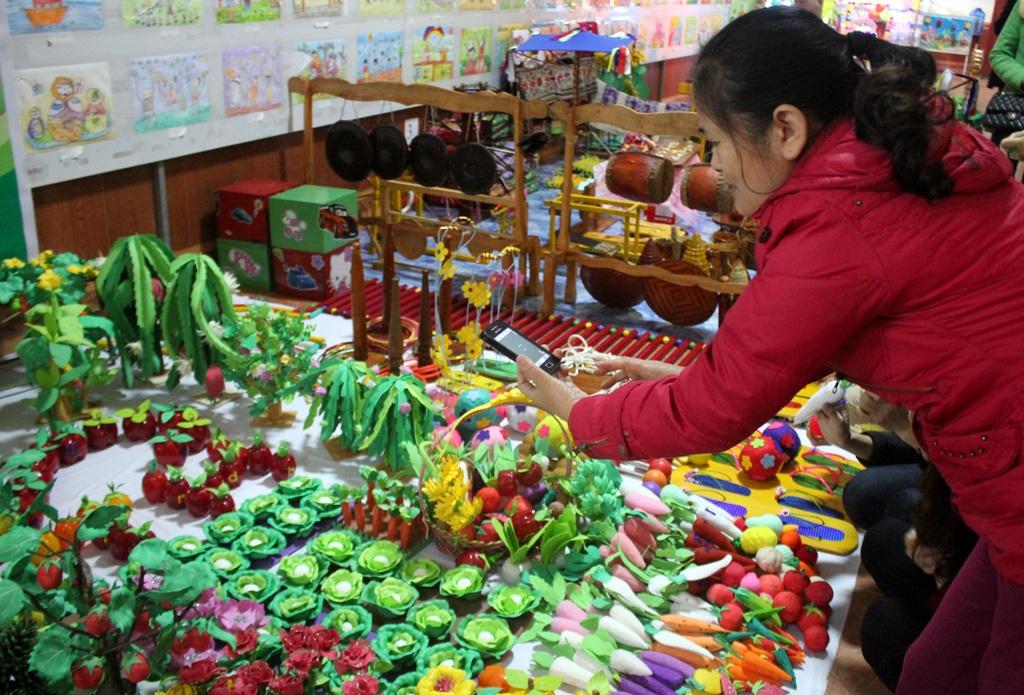 Một giáo viên mầm non đang lưu lại những hình ảnh về các sản phẩm đồ dùng đồ chơi trưng bày tại Hội thi.