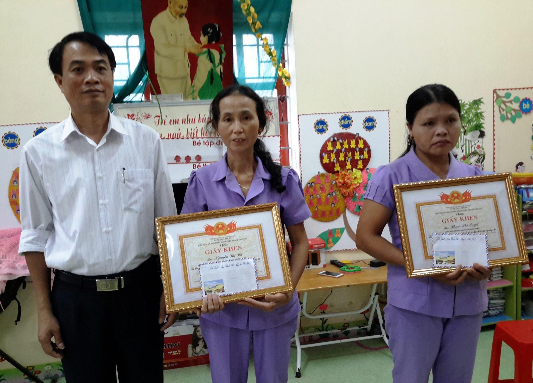 Thay mặt lãnh đạo huyện, ông Đặng Văn Hóa - Trưởng phòng GD huyện Thanh Chương trao Giấy khen cùng tiền thưởng cho 2 cô giáo mầm non xã Thanh Xuân.
