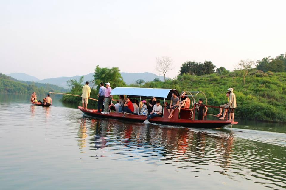 Du khách khám phá đảo chè bằng thuyền trên dòng nước xanh trong.