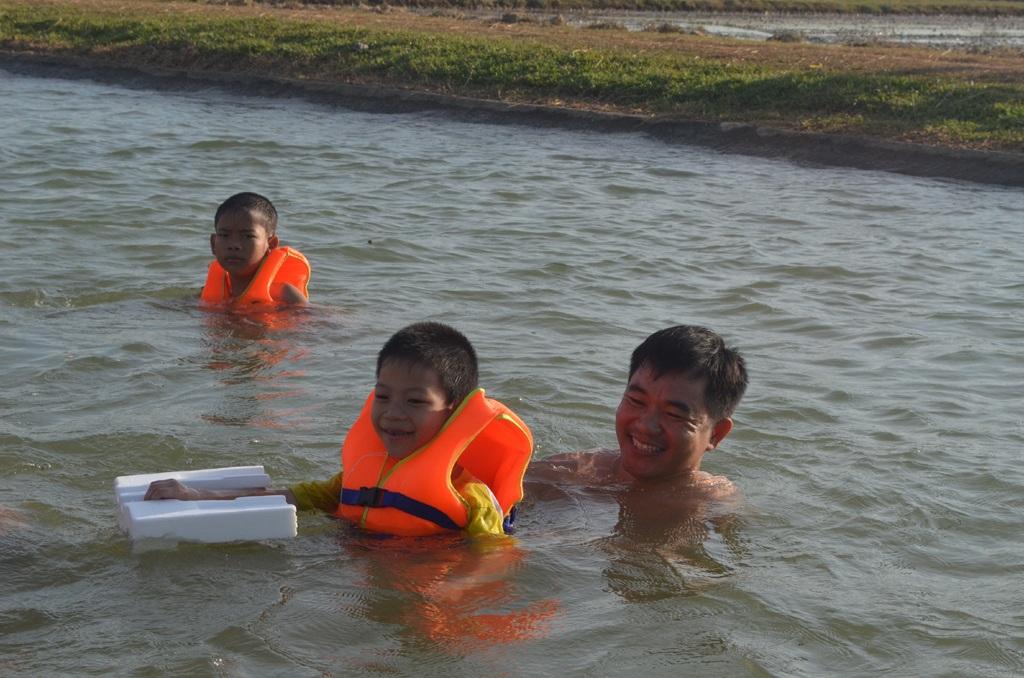 Phụ huynh ở Thanh Chương (Nghệ An) tập bơi cho con trên dòng nông giang dẫn nước ra đồng (ảnh minh họa).