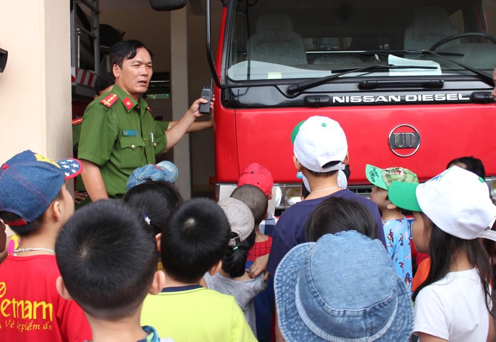 Các cháu học sinh được cán bộ Phòng PCCC số 1 - Cảnh sát PCCC Nghệ An giới thiệu về các phương tiện chữa cháy.