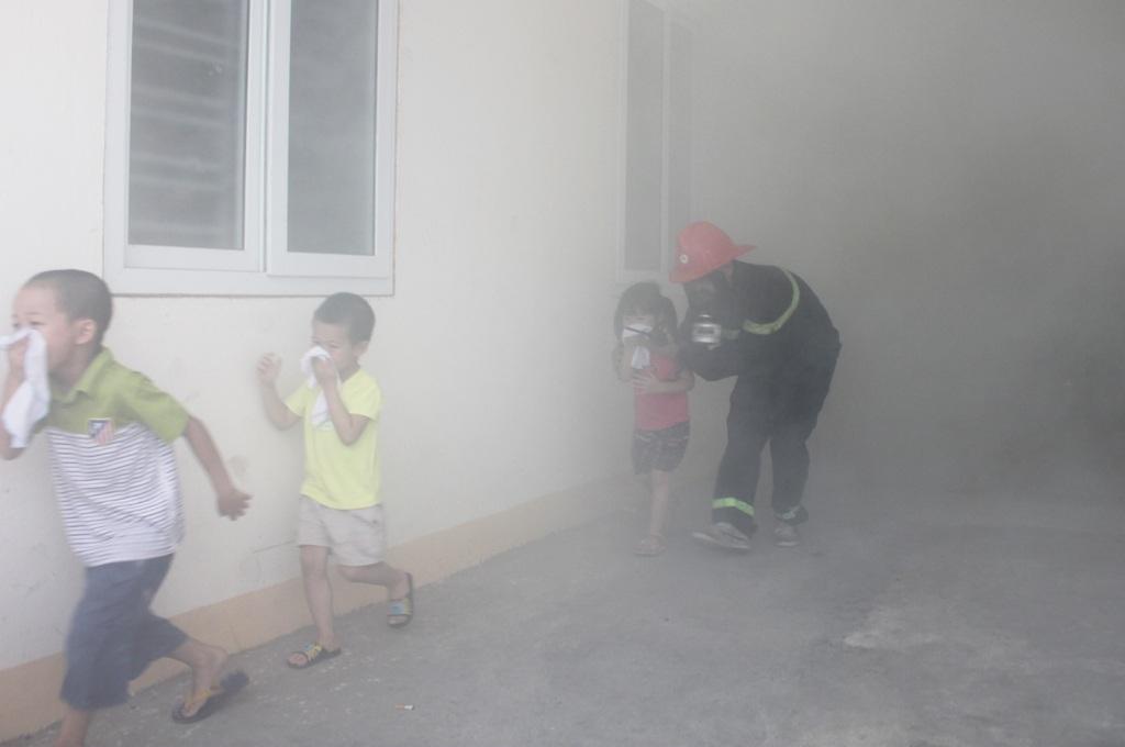 Một đám cháy giả định được bố trí trong khuôn viên trụ sở PCCC số 1. Các cháu nhỏ được hướng dẫn kỹ năng thoát khỏi đám cháy, tránh thương tích có thể xảy ra...