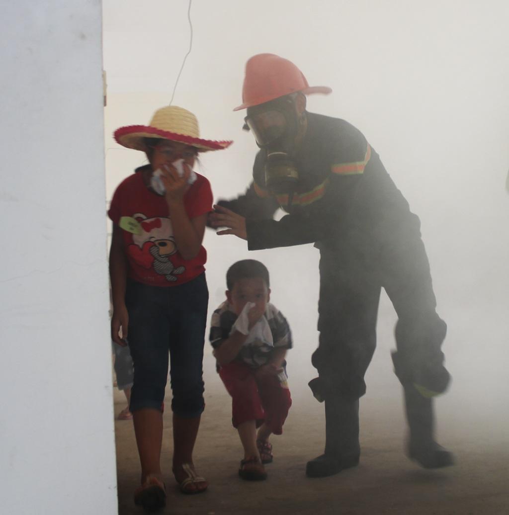 Theo hướng dẫn của các chú lính cứu hỏa, các em nhanh chóng thoát ra khỏi khu vực nguy hiểm.