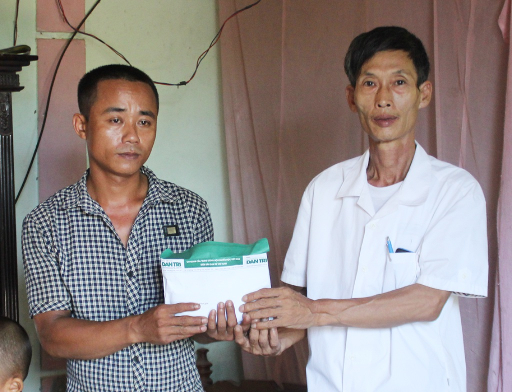 Ông Trương Văn Tuyền - Chủ tịch Hội chữ thập đỏ xã Nghi Văn trao số tiền độc giả Báo Dân trí ủng hộ tới gia đình anh Trương Văn Minh.