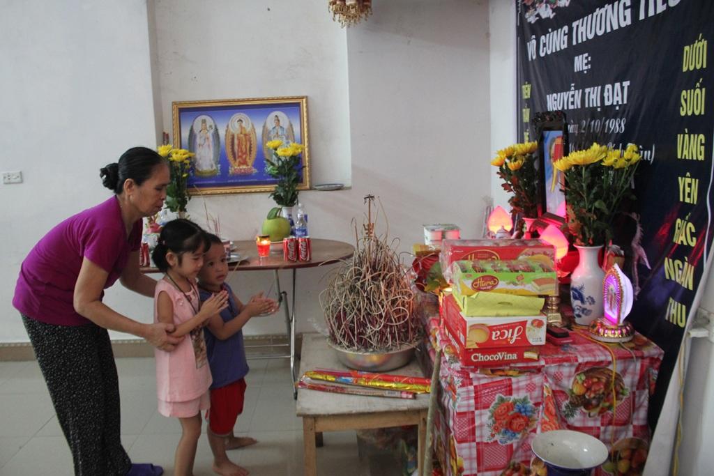Hai đứa trẻ nhỏ xíu ngơ ngác trước bàn thờ mẹ.