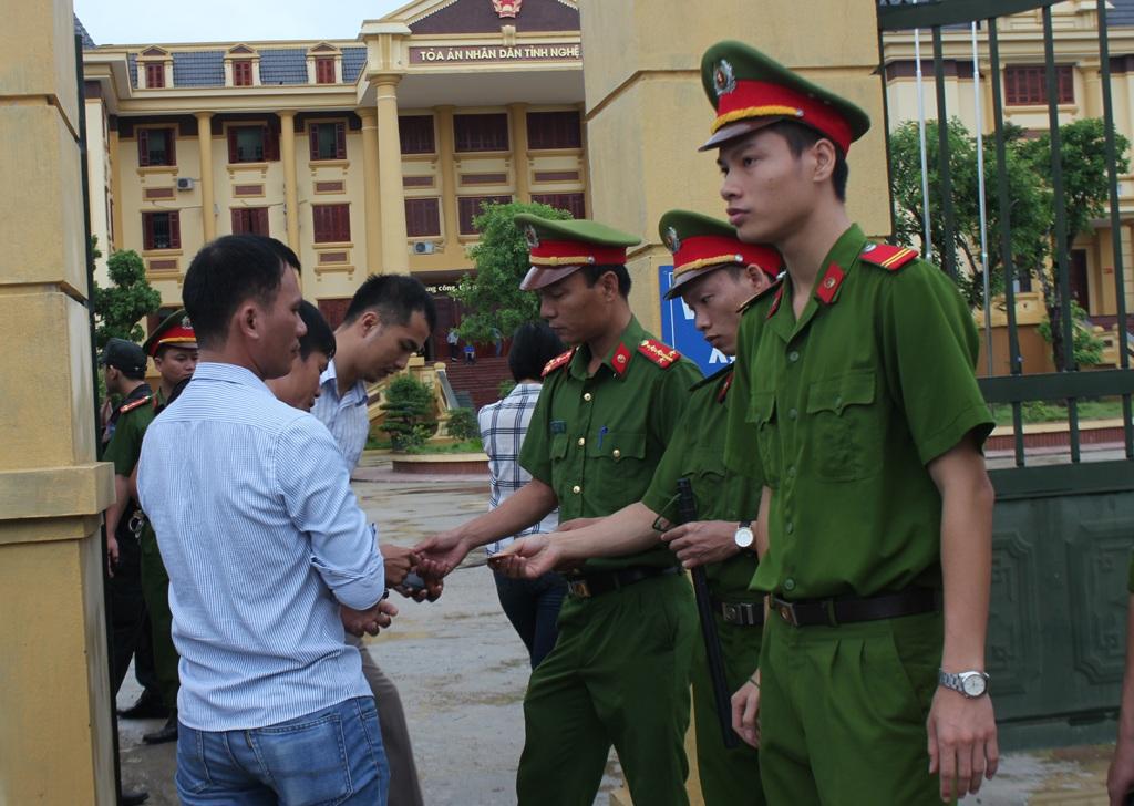 Lực lượng bảo vệ phiên tòa kiểm tra giấy tờ tùy thân của những người vào tham dự phiên tòa.