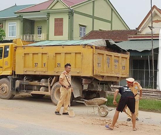Hai chiến sĩ CSGT cùng tài xế dọn số đất vương vãi trên mặt đường (ảnh Facebook).