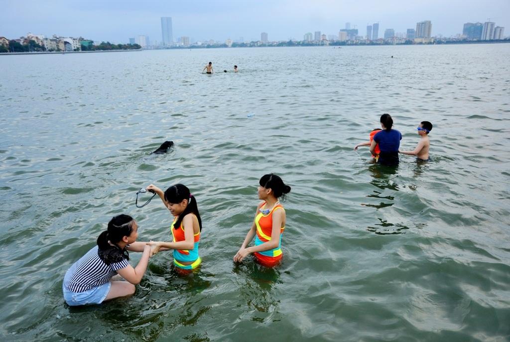 Nhiều người lớn tận dụng mặt hồ để dạy bơi cho trẻ.