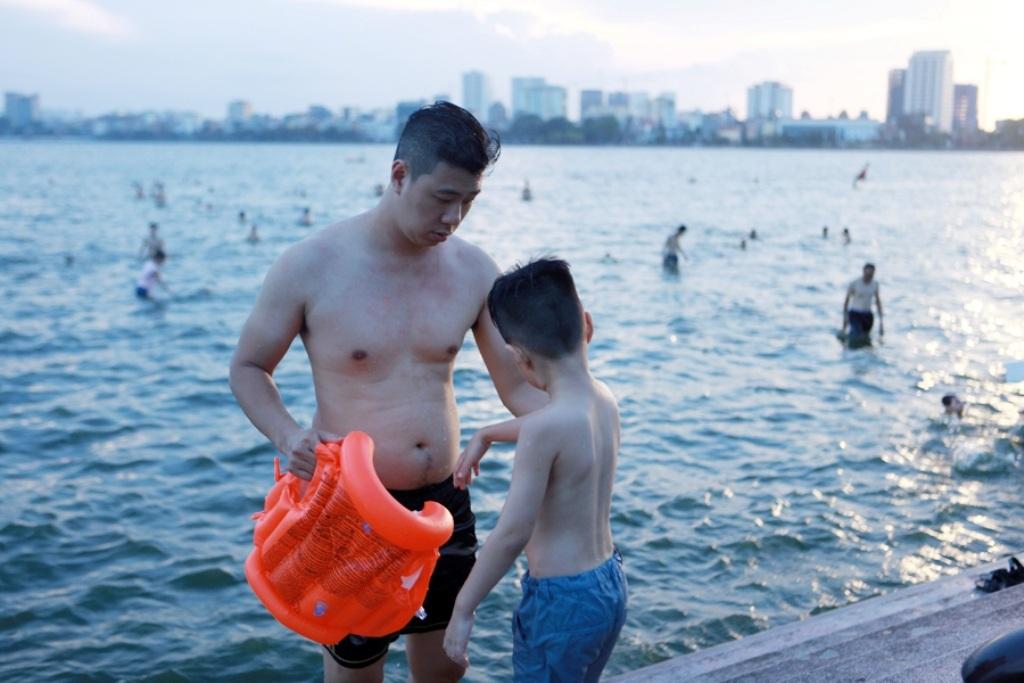Một em nhỏ được bố mặc phao bơi trước khi xuống tắm.