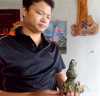 Anh Trần Công Viên đang cầm trên tay chiếc bình hồ lô được cho là cổ vật