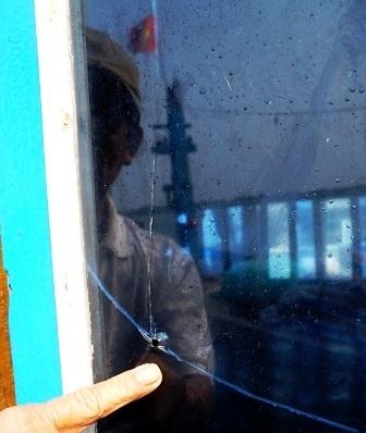 Vết đạn bi sắt bắn bể kính tàu cá QNa 91865