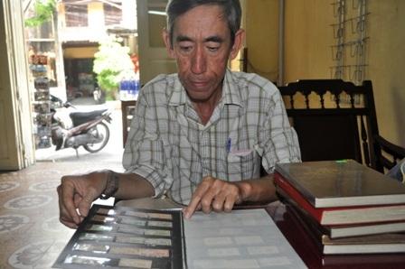 Ông Lưu Văn Tuyến với bộ sưu tập tem của mình
