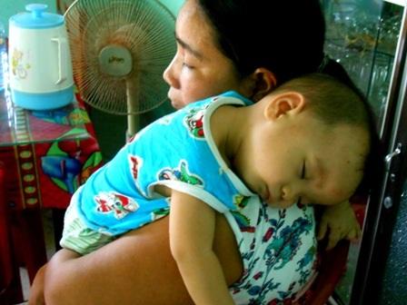 Bé Định Tạo ngủ trên vai mẹ sau một hồi mệt mỏi vì bệnh hành hạ, mô hôi em cứ chảy suốt dù nắng hay mưa, đã nhiều tháng tuổi nhưng Tạo vẫn chưa chập chững được như trẻ khác vì sức khỏe quá yếu