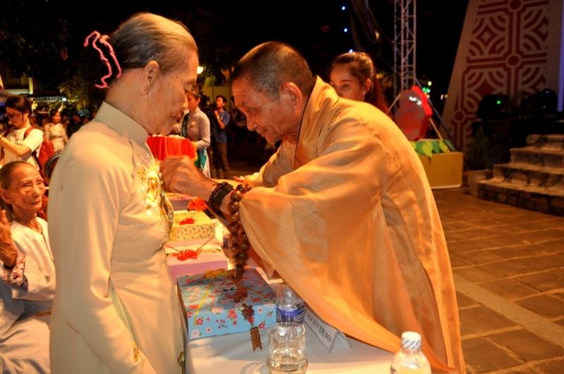 Sư thầy cài hoa hồng cho một trong những người mẹ được tri ân trong đêm hội