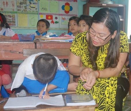 Cô Sành uốn nắn cho Tài viết chữ bằng chân trái.