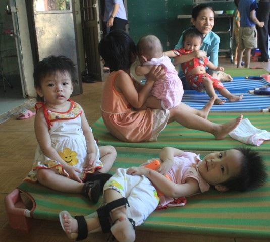 Em Phương Thảo (nằm) là trẻ khuyết tật, bị cha mẹ bỏ rơi từ nhỏ.