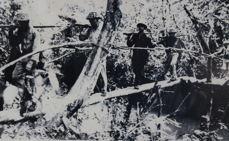 Giao bưu dẫn đoàn bộ đội hành quân qua suối