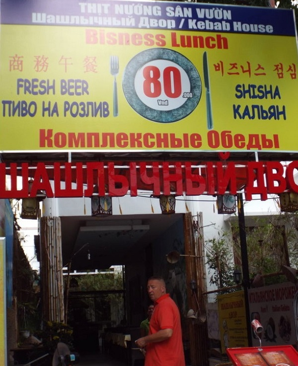 Các tiếng Trung Quốc và Nga to hơn rất nhiều so với tiếng Việt được ghi có vẻ rất hạn chế về số tiền ở giữa tấm biển quảng cáo