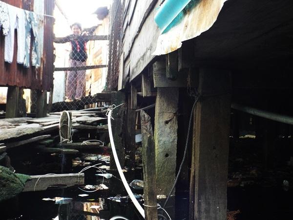 Những con đường được gia cố tạm bợ bằng những thanh gỗ sơ sài, gập ghềnh khó đi. Bên dưới là những vũng nước đen ngòm, rác thải bừa bộn