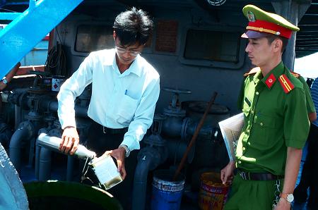 Cảnh sát kiểm tra số dầu lậu trên một tàu bị tạm giữ - Ảnh: H.X.