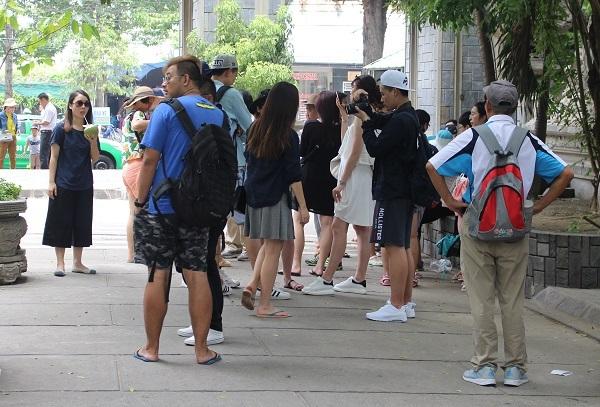 Hướng dẫn viên người Trung Quốc (áo xanh, dép lê) sau khị ống kính chụp vì thuyết minh trái phép ở chùa Long Sơn (TP Nha Trang) đã lẳng lặng bỏ đi - Ảnh: Viết Hảo