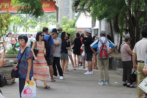 Một HDV Trung Quốc (áo xanh, đeo ba lô) giả vờ lơ sau khi bị ống kính chụp về hành vi thuyết minh trái phép ở chùa Long Sơn, TP Nha Trang - Ảnh: Viết Hảo