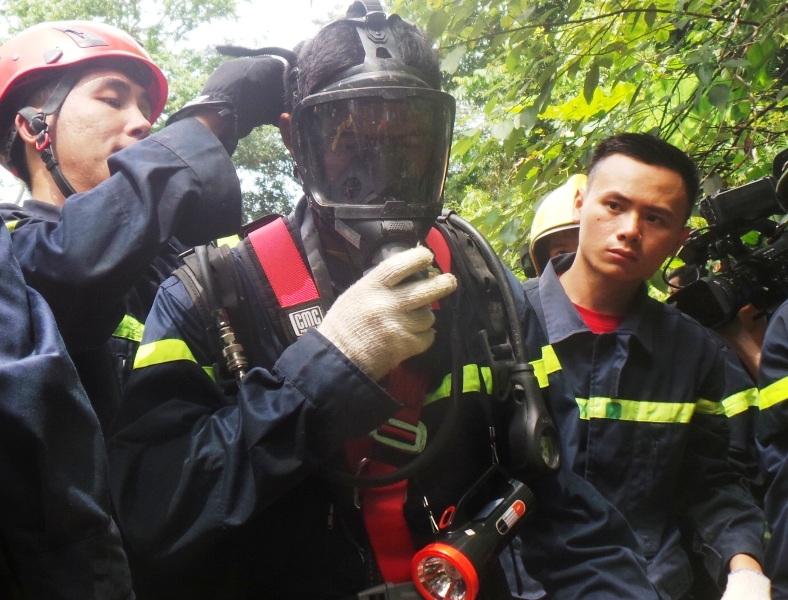 Chiến sĩ Cảnh sát PCCC đeo mặt nạ phòng độc và bình oxy để xuống hang
