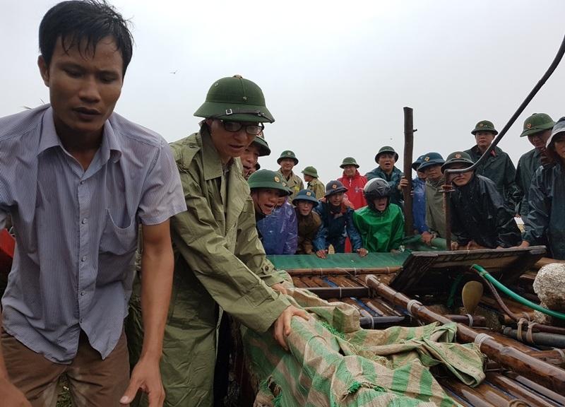 Phó Thủ tướng cùng đoàn công tác và người dân đẩy tàu vào bờ ở huyện Hoằng Hóa