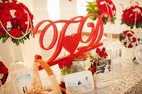 Không gian tiệc được trang trí khá nhẹ nhàng bởi gam đỏ trắng làm chủ đạo. Ảnh cưới của cặp uyên ương được đặt trang trọng trên bàn đón khách.