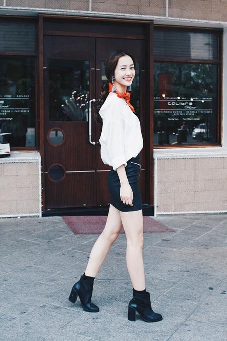 Set đồ streetstyle thứ hai, Jun Vũ nữ tính hơn với sơmi trắng thắt dây đằng trước cùng chân váy da và boot cao cổ.